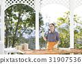テラスでペンキ塗りする女性 31907536