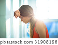 Tired businesswoman leaning on wall 31908196