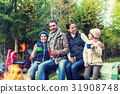 happy family sitting on bench at camp fire 31908748