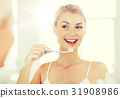 woman with toothbrush cleaning teeth at bathroom 31908986