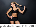 young woman in black sportswear posing in gym 31909903