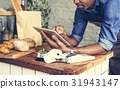 Adult Man Using Tablet in Bakery Shop 31943147