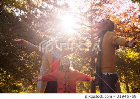 Family with arms outstretched against trees 31946769