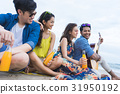 A man with a guitar is sitting on the beach with his friends 31950192