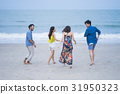 Two men and two women are walking, playing happily on the beach 31950323