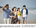 The two couples are happily walking along the beach 31950367