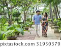 A photo of the couple with arm in arm walking in the garden 31950379