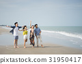 A photo of four friends standing and enjoying on the beach. 31950417