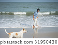 A photo of a man smiling and looking at a dog on the beach. 31950430