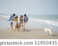A photo of four friends playing with dogs on the beach. 31950435