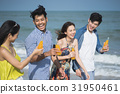 four people are smiling and drinking their bottles of juice on seaside 31950461