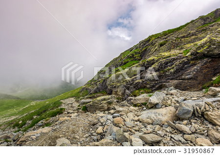 Steep slope on rocky hillside in fog 31950867