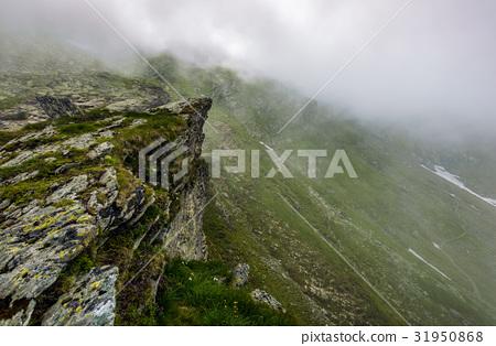 Steep slope on rocky hillside in fog 31950868