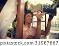 Woman hanging open board at the window 31967667