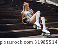 blond girl on roller skates sitting in a city park  of the rive 31985514