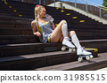 blond girl on roller skates sitting in a city park  of the rive 31985515