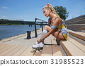 blond girl on roller skates sitting in a city park  of the rive 31985523