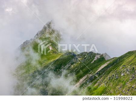 Steep slope on rocky hillside in fog 31998022