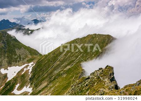 Steep slope on rocky hillside in fog 31998024