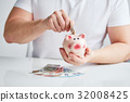 Male hand putting money into piggy bank 32008425