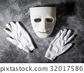 White mask with glove on gray grunge background. 32017586