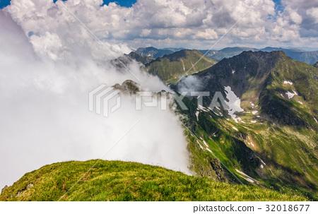 Steep slope on rocky hillside in fog 32018677