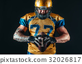 American football player holds ball in hands 32026817