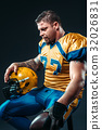 Football player with ball and helmet in hands 32026831