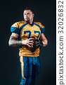 American football player poses with ball in hands 32026832