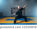Wushu fighter with sword in action, martial arts 32026836
