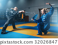 Wushu fighters, man with sword and woman with fan 32026847