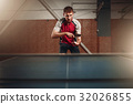 Man with racket in action, playing table tennis 32026855