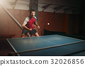 Man with racket in action, playing table tennis 32026856