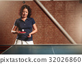 Table tennis, female player with racket hits ball 32026860