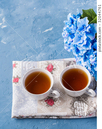 Cup of tea on blue background with flowers 32044761