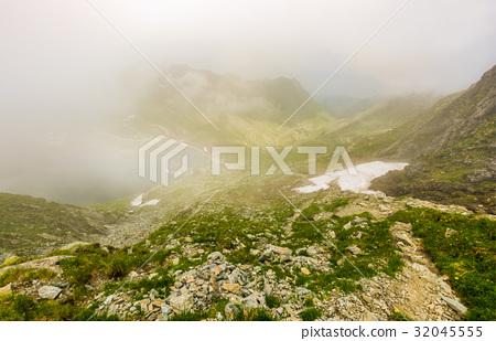 Slope on rocky hillside over foggy balea lake 32045555