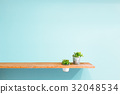 Wooden shelf on blue vintage wall with green plant 32048534