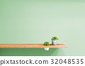 Wooden shelf on green vintage wall with plant. 32048535