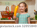 child girl with vegetables in kitchen interior 32055840