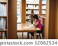 Female student reading book in college library 32062534