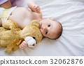 Baby lying on baby bed 32062876