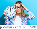 Woman holding clock showing nearly 12 32082499