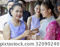 A woman is giving something to a girl 32090240