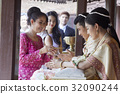 A woman is performing ritual with a groom at the wedding ceremony. 32090244