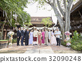 Groom and bride are taking photo with their guests at their wedding ceremony.  32090248