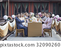 Guests are holding wine glasses and smiling at a wedding ceremony 32090260