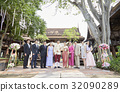bride and groom are standing with guests in line  in the garden  32090289