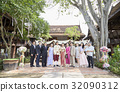 the bride and the groom are standing in line with their relatives and smiling 32090312