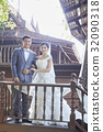 A wedding couple is standing closely and smiling at the balcony 32090318