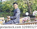 Young man in tuxedo is sitting at the balcony and looking at something 32090327